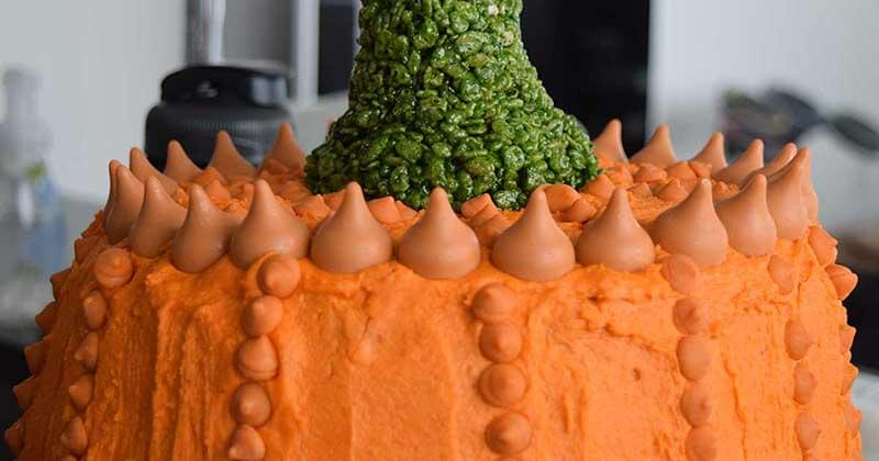 Close-up of the top of an orange pumpkin cake with a green stem made from rice cereal.