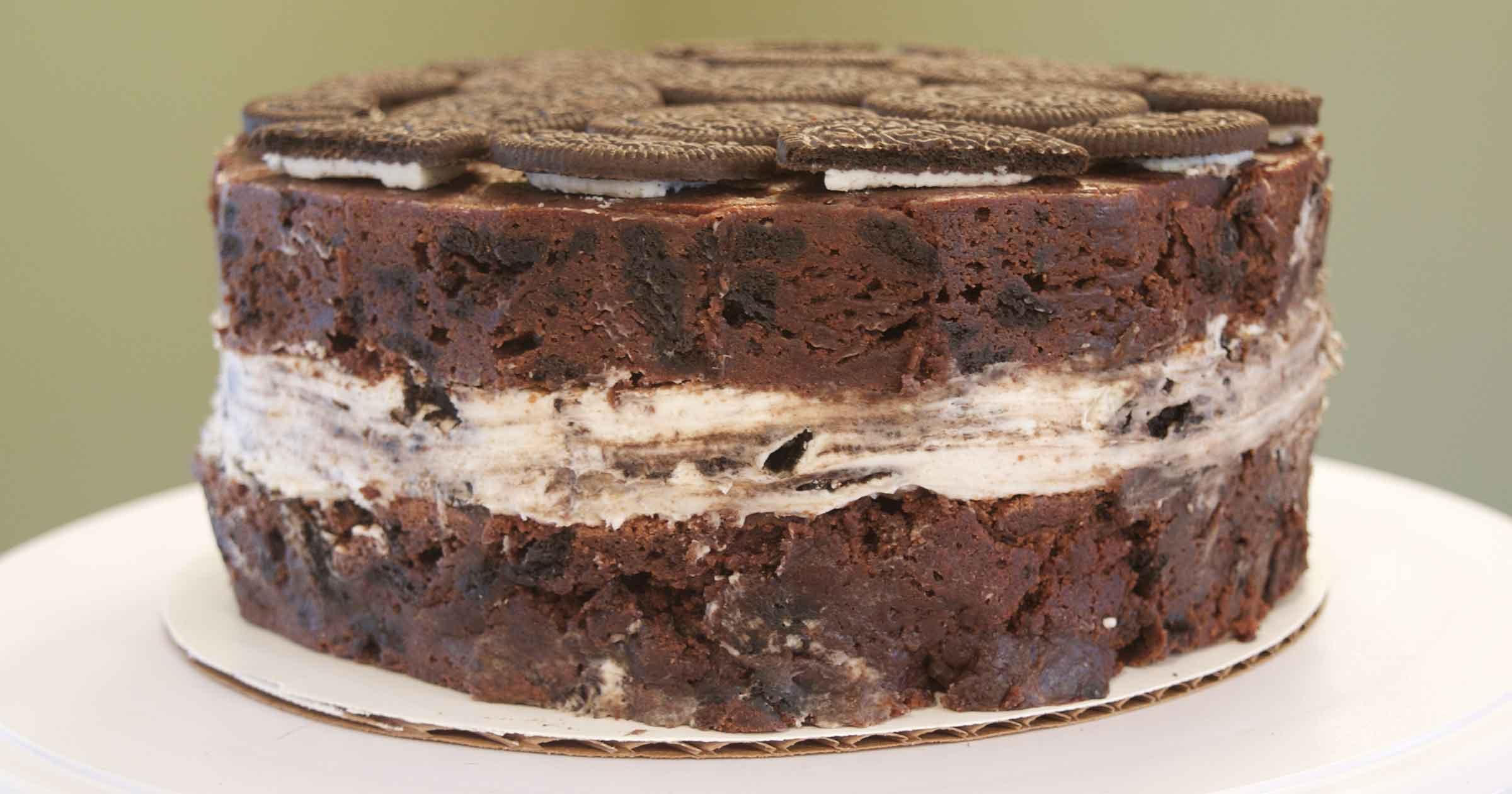 9-inch circular brownie cake that looks like a giant, thick sandwich cookie with creme filling, shown from the side